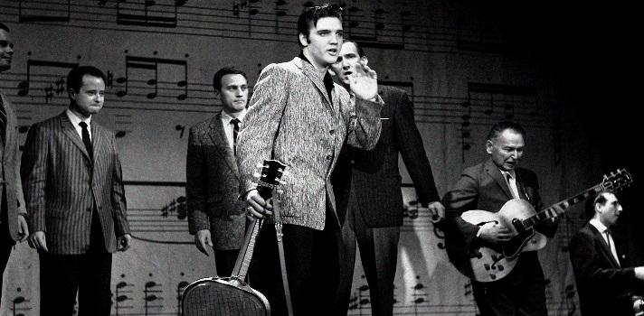 """<div align=justify><strong>¿Cómo comenzó Elvis Presley?</strong><br/><br/> Tres décadas después de su muerte <strong>Elvis Aron Presley </strong>continúa siendo una <strong>leyenda del rock mundial</strong>. <a href=https://noticias.universia.net.mx/cultura/noticia/2016/01/08/1135216/6-curiosidades-elvis-presley-aniversario-nacimiento.html title=6 curiosidades sobre Elvis Presley en el aniversario de su nacimiento target=_blank>Nacido en <strong>Tupelo (Mississipi)</strong> un <strong>8 de enero de 1935</strong></a>, Elvis recibió de regalo su primera guitarra a los diez años de edad, aunque en varias oportunidades confesó que en aquel momento hubiera preferido una bicicleta. Meses más tarde, sus tíos y el pastor de la iglesia le impartieron algunos conocimientos elementales sobre cómo tocar este instrumento. <br/><br/> A los 13 años de edad su familia se trasladó a la ciudad de <strong>Memphis (Tennesee)</strong>, donde el joven de ojos melancólicos descubrió su <strong>gusto por el blues de los negros</strong>. Una vez finalizó la escuela secundaria, comenzó a trabajar como chofer de tractor en una compañía de electricidad. <br/><br/><strong>Su primer contacto directo con la música fue en julio de 1953</strong>, cuando en la compañía de discos <strong>Sun Records</strong> decidió grabar la <strong>canción """"My Happiness"""" </strong>como regalo de cumpleaños para su madre. Tan sólo un año más tarde, volvería a grabar un disco que incluiría canciones como<strong> """"Amor de ocasión"""" y """"Nunca permaneceré en tu camino""""</strong>, interpretaciones que llamarían la atención del promotor <strong>Sam Phillips</strong>. <br/> <br/><strong>Elvis Presley alcanza la cima del éxito</strong><br/><br/><strong>El año 1956 sería decisivo en la carrera de Presley</strong>, dado que grabaría por primera vez en los estudios neoyorkinos de la RCA su versión de la canción de <strong>Carl Perkins</strong><strong>""""Blue Suede Shoes""""</strong>, junto con otras siete canciones más que darían como """
