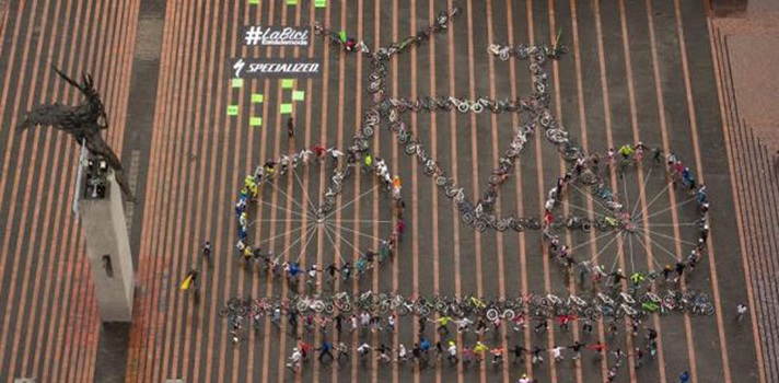 <p style=text-align: justify;>Manizales fue el escenario de este nuevo récord mundial en el que –durante el Día Mundial de la Bicicleta- se llevó a cabo el evento, organizado por el movimiento 'La Bici está de Moda'.</p><p style=text-align: justify;></p><p style=text-align: justify;>La figura humana con 130 ciclistas y sus bicicletas entre ellas de Specialized se enviarán al comité de los Guinness Records para que avalen esta actividad que se logró gracias a una sencilla ejecución y planeación que sólo duró 15 días a través de voz a voz que incluyó lugares como el cable y la plaza.</p><p style=text-align: justify;></p><p style=text-align: justify;>En la Plaza de Bolívar, se trazó una bicicleta con cinta en el piso para lograr una bicicleta humana de 36 metros de largo x 24 metros de ancho que estaría muy por encima de otra bici en Harvard que es metálica y mide 4.5 metros.</p><p style=text-align: justify;></p><p style=text-align: justify;>Ahora el logro corresponde a validar el título de la bicicleta más grande ante la organización Guinness Records, por un valor de 4 mil dólares unos $ 10 millones aproximadamente.</p><p style=text-align: justify;></p><p style=text-align: justify;>El movimiento la bici está de Moda organiza el evento El Tour de la Esperanza que se realiza cada 15 días los fines de semana, haciendo recorridos por varios municipios del departamento de Caldas donde han logrado concertar a 200 riders.</p><p style=text-align: justify;>Para el director de la oficina de la bici Carlos Mario Marín, la bicicleta está transformando ciudades y permite a los manizalitas disfrutar de un aire más limpio.</p>