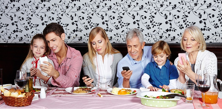 Sin importar la edad, la mayoría de los integrantes de la familia revisa su celular en la mesa