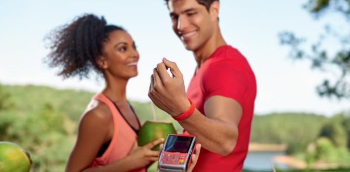 <p dir=ltr><strong>O que é a tecnologia NFC?</strong></p><b><b><br/></b></b><p dir=ltr><span>O NFC (</span><span>Near Field Communication</span><span>; em português: campo de comunicação de curta distância) é uma tecnologia que permite a troca de informações entre aparelhos que estejam próximos um do outro. Diferente dos cartões magnéticos ou com chip, que precisam ser 'passados' ou inseridos na máquina, as soluções que utilizam a tecnologia NFC requerem apenas que o dispositivo esteja a uma curta distância da maquininha, não mais do que alguns centímetros.</span></p><b><b><br/><br/></b></b><p dir=ltr><strong>Como funciona o sistema de pagamento via NFC</strong></p><b><b><br/></b></b><p dir=ltr><span>Hoje, a tecnologia NFC está sendo utilizada como uma alternativa de pagamento móvel, sendo uma solução complementar aos cartões de crédito e de débito. Sua vantagem está na rapidez e na conveniência. </span></p><b><b><br/></b></b><p dir=ltr><span>Imagine, por exemplo, que você quer ir para praia levando do hotel o mínimo de coisas com o que se preocupar. Não quer ficar pensando na carteira ou no celular antes de entrar no mar ou fazer uma corrida pela orla. Graças ao sistema de pagamento via NFC, hoje você pode vestir uma pulseirinha à prova d'água, pode entrar com ela no mar sem se preocupar e, na saída, comprar uma água de coco ou um picolé apenas aproximando o seu pulso da maquininha do vendedor. </span></p><b><b><br/></b></b><p dir=ltr><span>No Brasil, mais de 70% dos estabelecimentos comerciais já aceitam essa modalidade de pagamento, e o número não para de crescer. Cada vez mais, micro e pequenos empreendedores, que atuam na venda de produtos de pequeno valor, estão aderindo ao novo sistema para receber pagamentos.</span></p><b><b><br/><br/></b></b><p dir=ltr><strong>O pagamento por NFC é seguro?</strong><span></span></p><b><b><br/></b></b><p dir=ltr><span>No sistema de pagamento via NFC, a transmissão de dados é feita apenas do dispositivo do cliente para a maqui