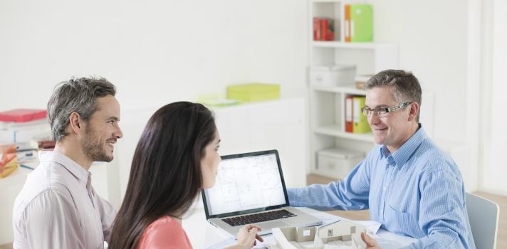 Asesor financiero aconsejando y ayudando a una pareja en la compra de su casa