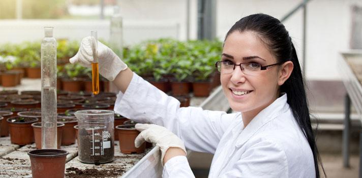 Bióloga realizando un experimento con plantas y sustancias químicas