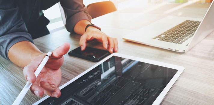 Hombre diseñando un sitio web usando distintos dispositivos tecnológicos